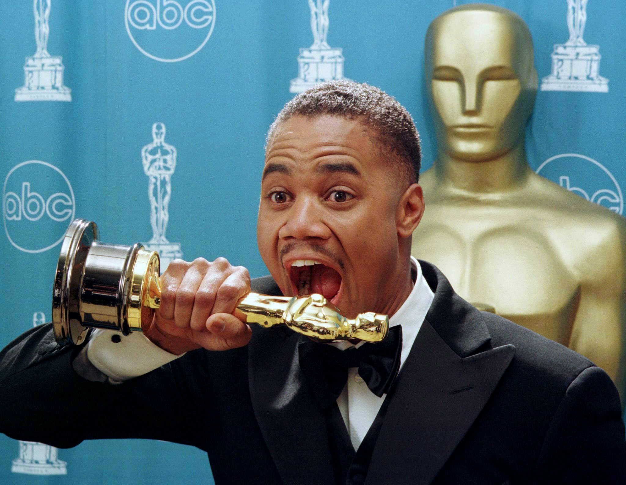 Best Supporting Actor Cuba Gooding Jr. pretends to bite into his Oscar statue after he won the award..