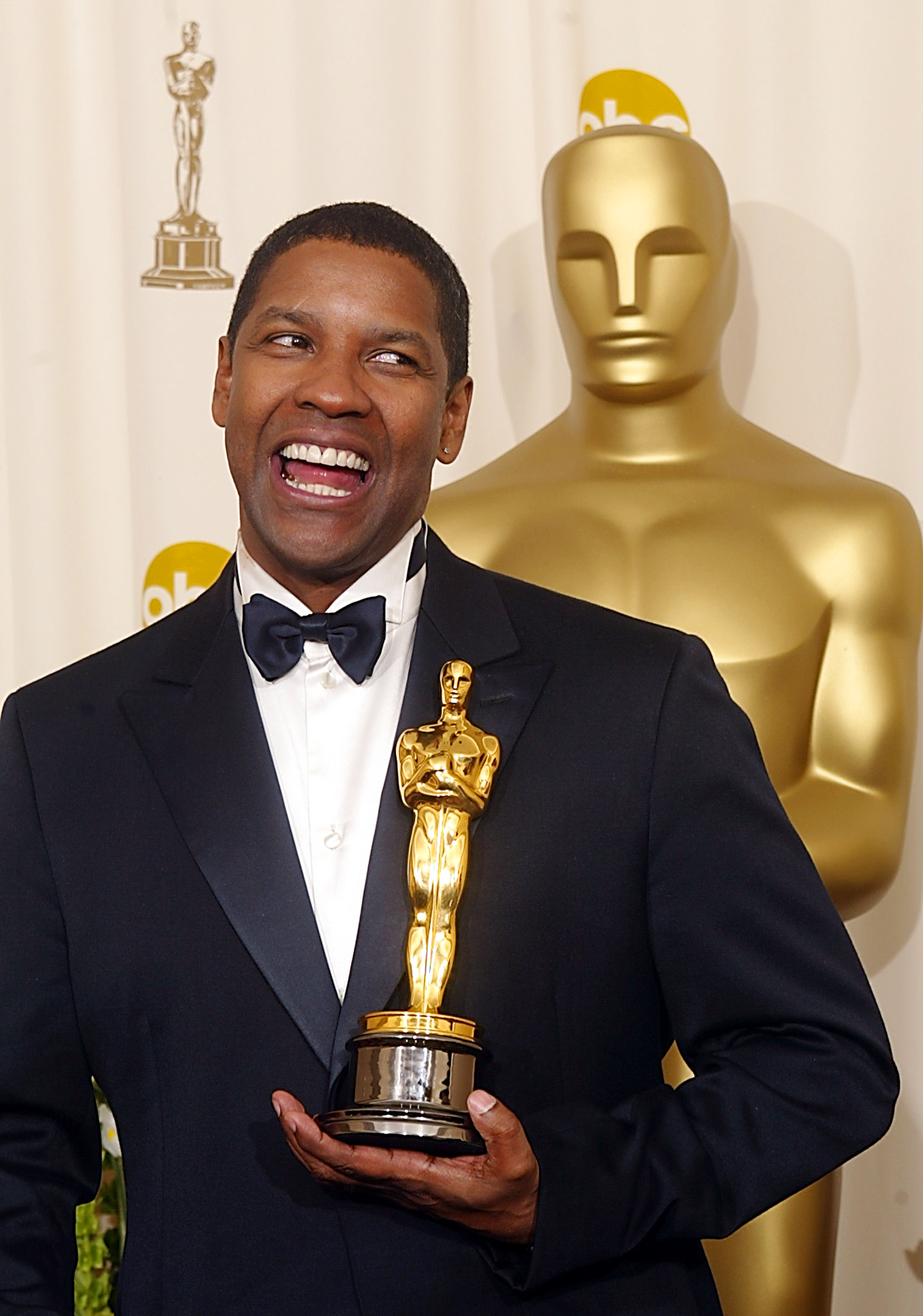 US actor Denzel Washington holds his Oscar  after