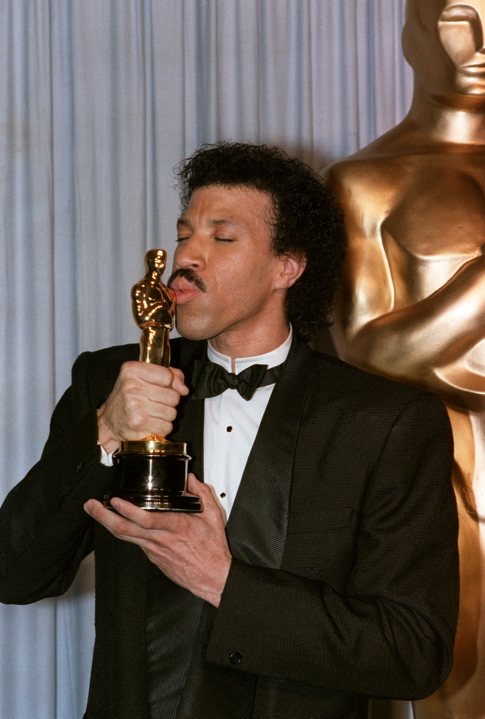 US singer Lionel Richie kisses his Oscar after he