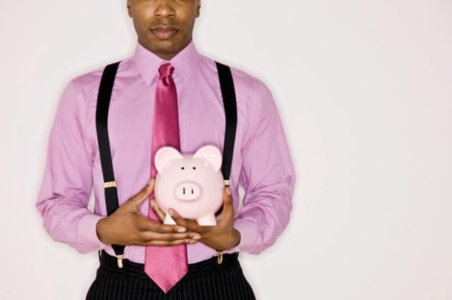 Confident businessman holding piggy bank