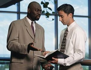 Black man mentoring young co-worker
