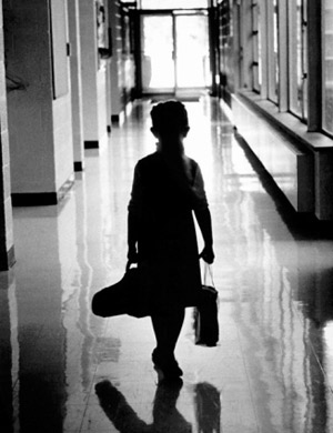 Young child holding instruments walking down school hallway
