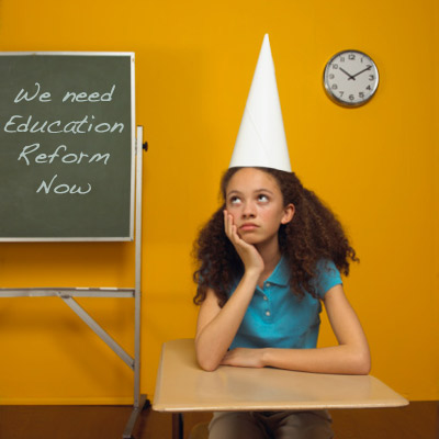 student in dunce cap writing that we need school reform