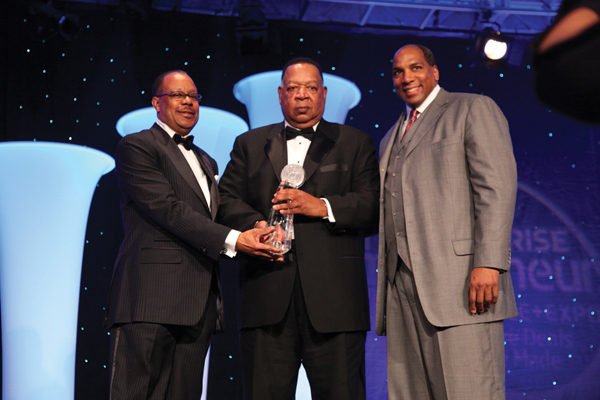 "PRWT Services Inc. CEO Harold T. Epps and Co-Founder Willie F. Johnson accept the BE 100s Company of the Year Award from Black Enterprise CEO Earl ""Butch"" Graves Jr."