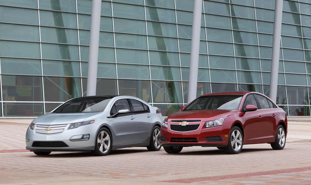 (L-R) 2011 Chevrolet Volt (pre-production model) and 2011 Chevrolet Cruze. The Volt is an electric car that can create its own electricity. Plug it in, let it charge overnight, and it's ready to run on a pure electric charge for up to 40 miles. The Volt uses a gas generator that produces enough energy to power it for hundreds of miles on a single tank of gas. (Image source: GM)