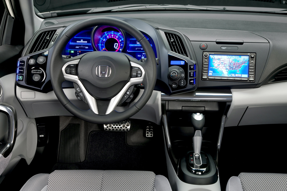 The two-passenger Honda CR-Z comes standard with a feature that allows the driver to select between sport, economy, and normal driving modes. The upper portion of the dashboard extends toward the driver in a wrap-around cockpit environment. (Image source: Honda)