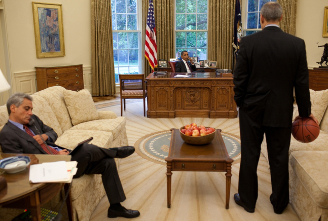 President Barack Obama and Chief of Staff Rahm Emanuel hold a conference call with House Speaker Nancy Pelosi and Senate Majority leader Harry Reid in the Oval Office, July 17, 2009.  Phil Schiliro, assistant to the President for Legislative Affairs, palms a basketball at right. (Source: White House)