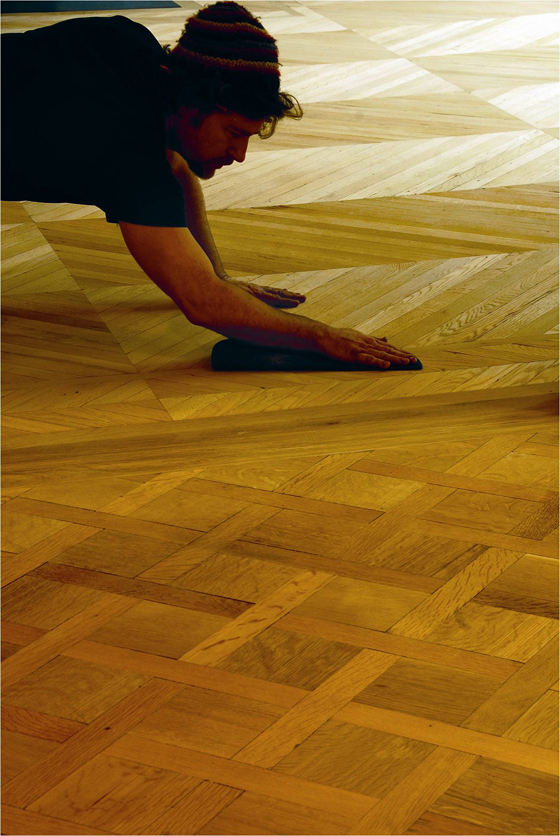A worker sands the floors, which are made from reclaimed wood.  (Image source: Kennedy Green House)