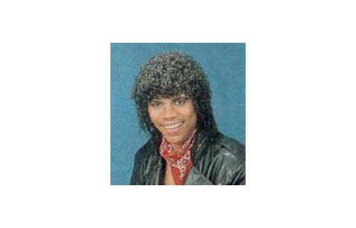 In 1977, the Jheri-mack curl emerges as new hairstyle trend in California. The ultra-moist curly perm grows in popularity through the nation and becomes prominent during the 1980s. As a result, it catapulted a number of black haircare companies to BE 100s status. (Image: 80s actor Stoney Jackson sporting a Jheri Curl)