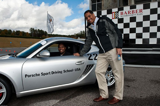 Bart Williams, Partner, Munger, Tolles, & Olson LLP (seated) and Charles H. James III, CEO, C.H. James Restaurant Holding L.L.C. (standing) enjoy themselves at the Barber Motorsport Park, home to the Porsche Sport Driving School