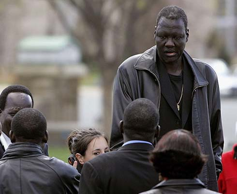 "Manute Bol (October 16, 1962 – June 19, 2010) A Sudanese-born basketball player and activist, Bol was one of the two tallest players ever to appear in the National Basketball Association at 7 feet, 7 inches, and was also the first African-born player to be drafted into the NBA. He was the son of a Dinka tribal chief, who gave him the name ""Manute,"" which means ""special blessing."" Bol truly lived up to his name off the court. Active in charitable causes throughout his career, he spent much of the money he made during a 10-year NBA career supporting various causes related to war-ravaged nation Sudan, eventually establishing the Ring True Foundation to raise funds for Sudanese refugees. Bol, who spent three years as a slave in childhood, helped create the Sudan Freedom Walk to find a solution to the genocide in Darfur in western Sudan, and also to raise awareness of the modern day slavery and human rights abuses throughout Sudan."