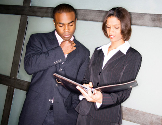African-American business man and woman reading