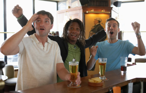 Men Watching the Game at Sports Bar and Drinking Beer