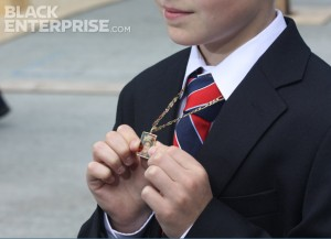 Young boy at 9/11 memorial wreath ceremony holding pendant with dead soldier's picture