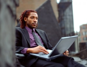african american man with dreads using laptop while wearing a suit