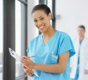 African American nurse smiling while holding medical chart