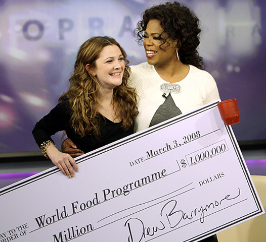 Oprah Winfrey recieving a $1 million dollar check from Drew Barrymore
