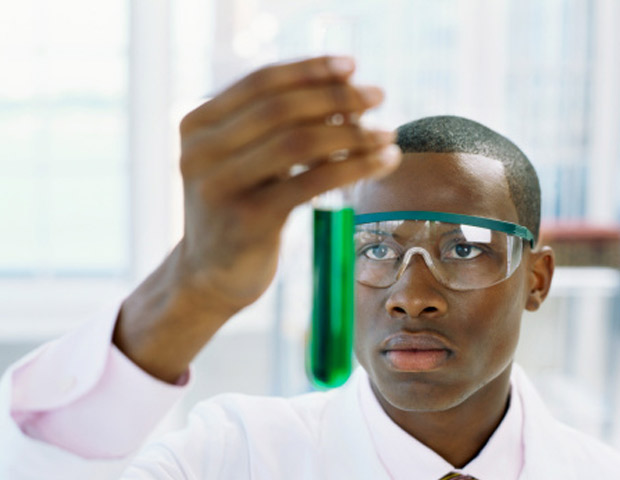African American holding a test tube looking at green liquid