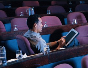 Man using a tablet in empty auditorium