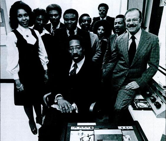 UNITY BROADCASTING: Eugene D. Jackson (seated), co-founder of Unity Broadcasting (1971), parent company of National Black Network. Jackson founded the company with Sydney Small (standing, 8th from left) and Del Raycee (standing, 9th from left). Unity and NBN offered news distribution services to black stations.