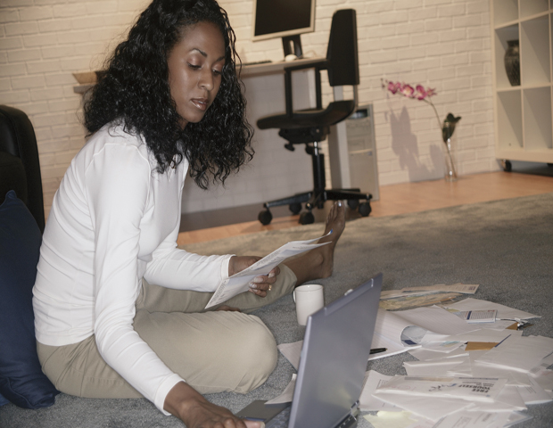 young woman sitting on the floor with a laptop, surrounded by papers