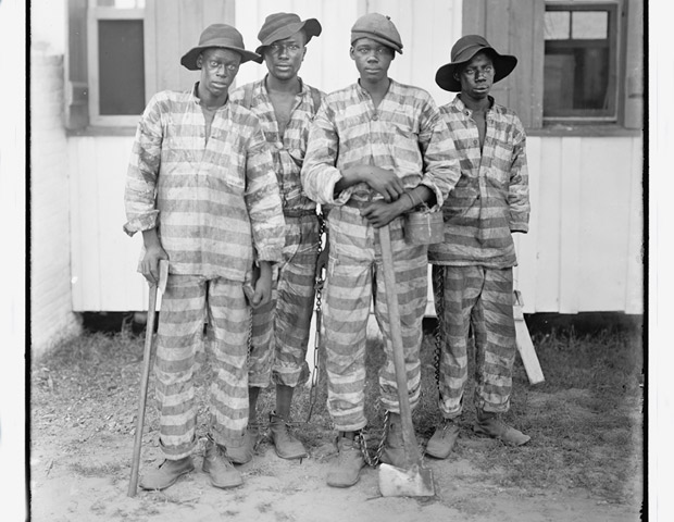 Archival photo of Black convicts in prison stripes