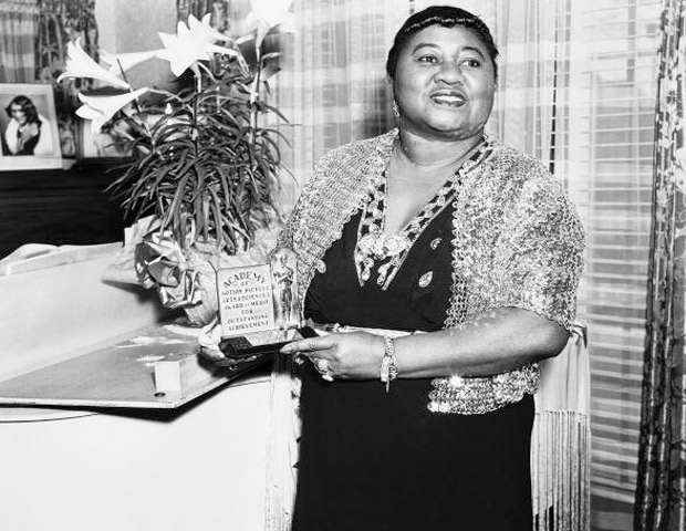 """HATTIE MCDANIEL  At the age of 47, Hattie McDaniel became the first African American to win the coveted Oscar for Best Supporting Actress for her portrayal of Mammy in Gone with the Wind (1939). It was a role that she was paid just $1,000 a week during the film's six-month production. Born to perform, McDaniel went on to have a successful career as an actress that was financially stable. In 1942, she purchased an impressive two-story, 17-room Hollywood mansion. She was known for her yearly parties. In her lifetime, McDaniel was cast in over 300 films but given screen credit in about 80, most of which were roles as domestics. When criticized by the NAACP for playing such roles she said, """"I could either get paid $100 a month as a real maid or $750 a week playing one in the movies!"""" Despite evidence that McDaniel had made a good living as a performer, her final estate was estimated at only $10,000."""