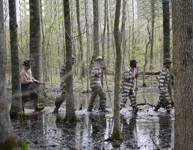 A reenactment scene from Slavery By Another name of convicts being escorted through the swamp