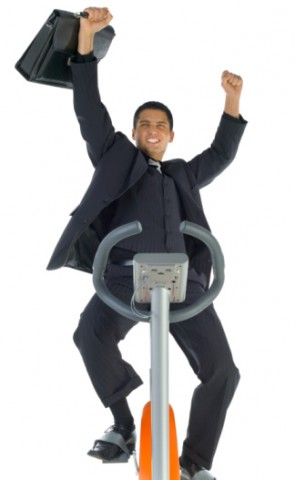 man in business suit on eliptical machine