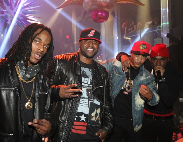The Dope Crew poses with Rico Love and T.I. on stage