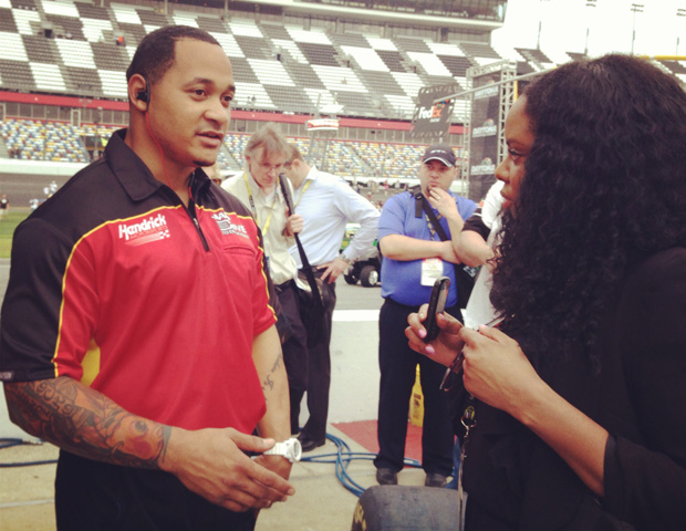 Janell Hazelwood interviews front tire carrier, Dion Williams, an ex-NFL player and alumnus of NASCAR's 'Drive for Diversity' program