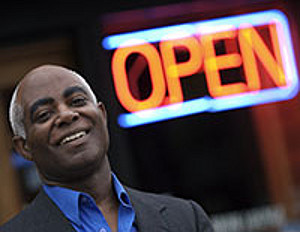 black man in front of store open sign