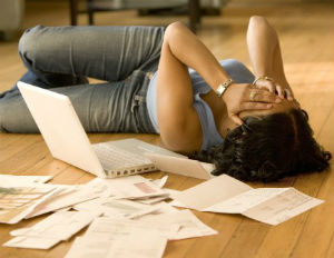 woman on floor worrying about bills
