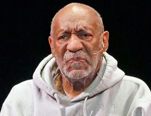 Bill Cosby wearing a grey sweatshirt and a lavalier mic