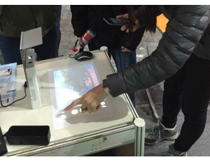 People test out the Lazertouch at a recent tech expo. (Image: Easitech, Indiegogo)